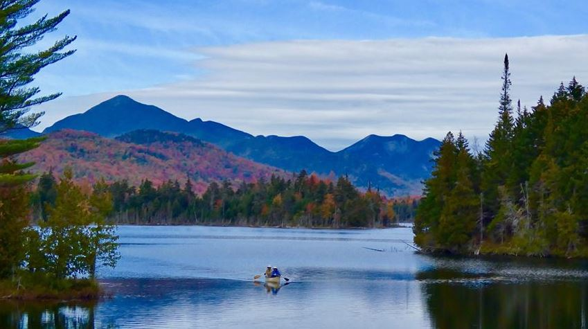 Canoe on a pond with fall foliage and mountains