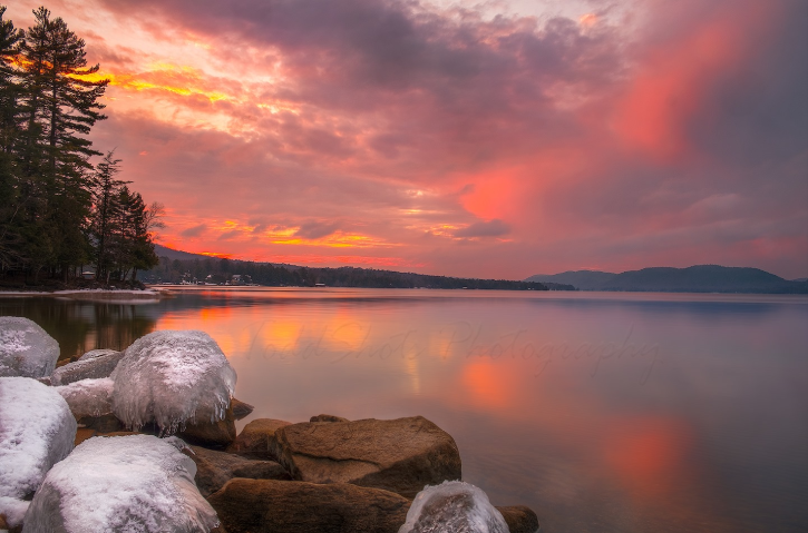 Vibrant pink sunset over a lake during the winter