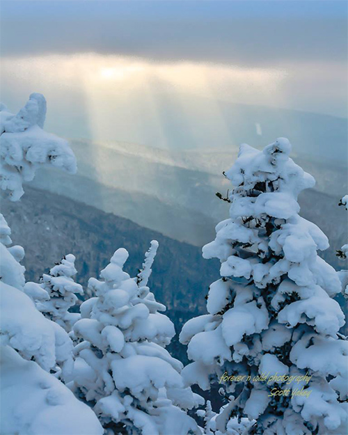 sunbeam over cascade mountain summit in winter
