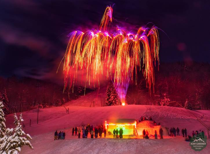 Pink & orange fireworks over igloo with bystanders