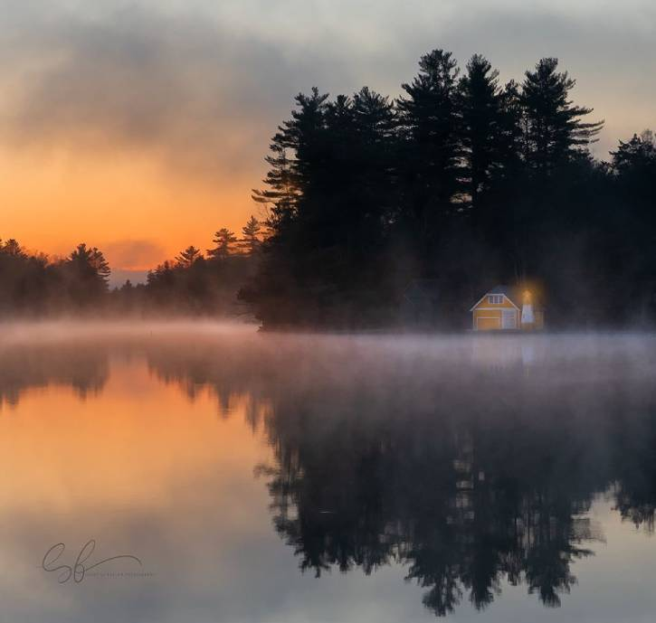 Orange sunrise over a pond with fog & yellow house