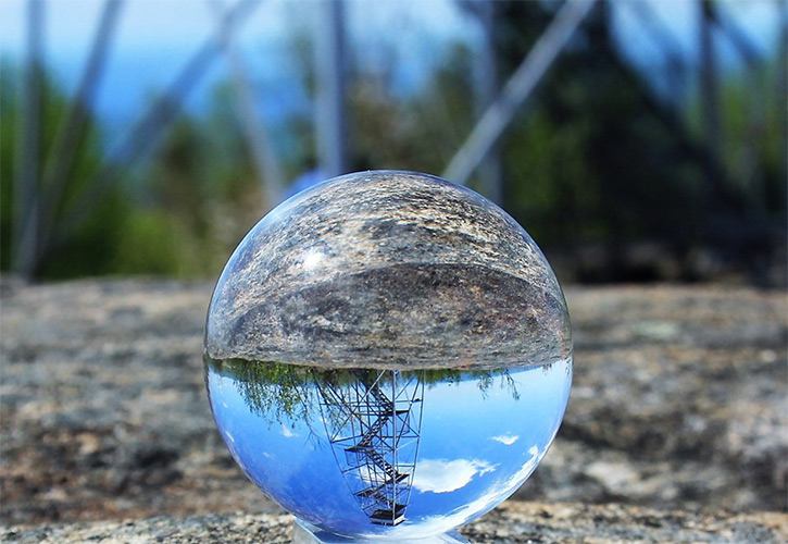 fire tower reflected in glass ball