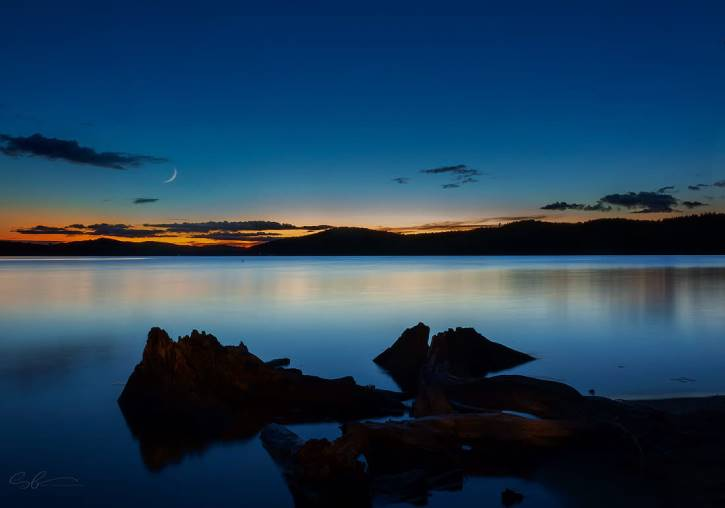 Blue and orange sky with crescent moon over lake