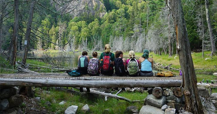 five campers and a counselor sitting on a log in the woods