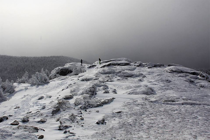 two people on a mountain summit in winter