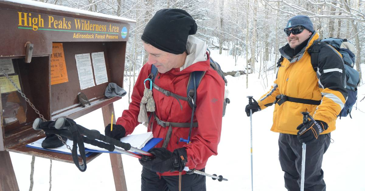 two winter hikers signing in at a trailhead