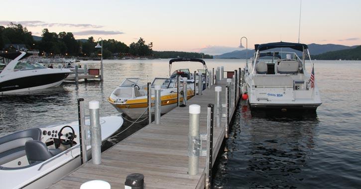 many boats near a dock on a lake