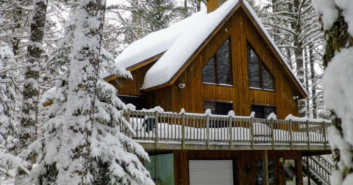 large cabin covered in snow