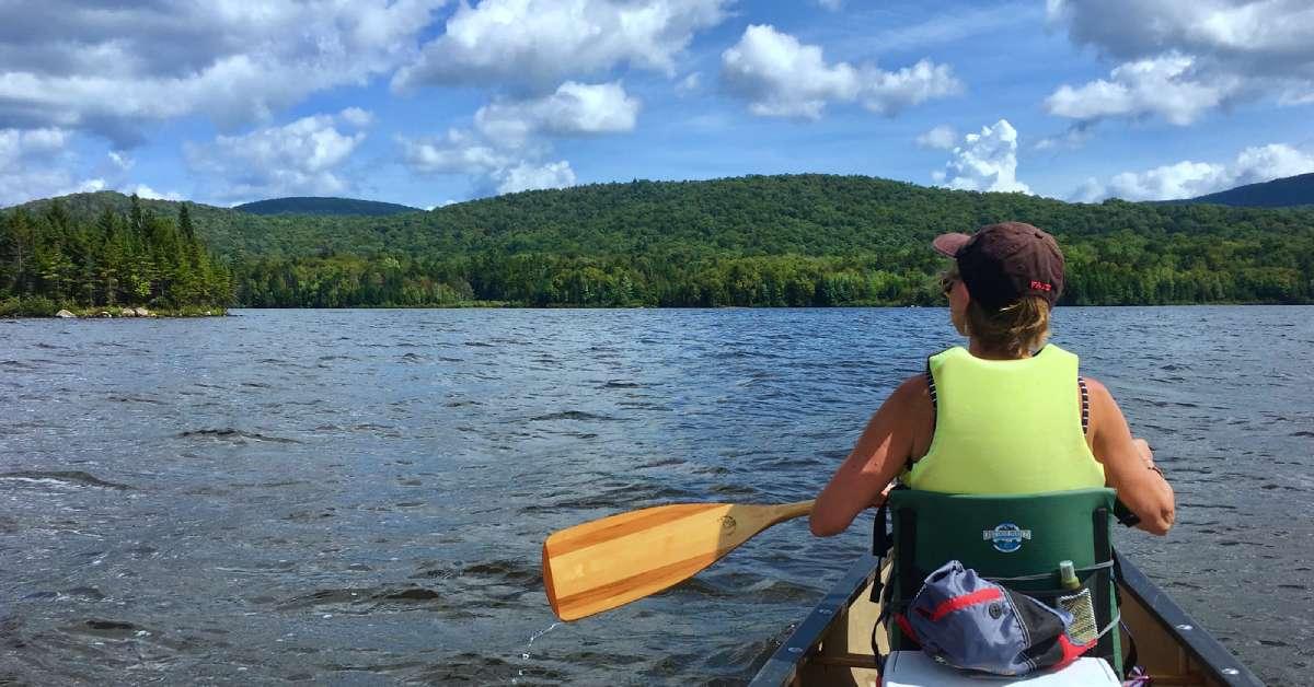 a woman canoeing on an adirondack lake