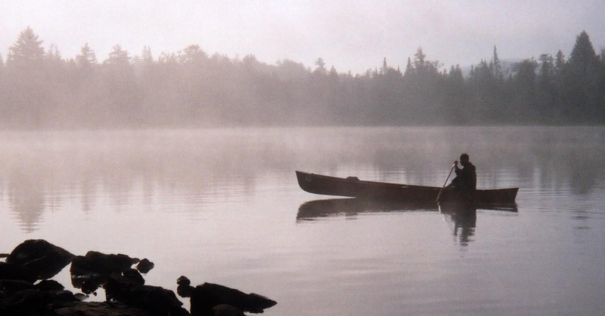 a canoe on a misty pond