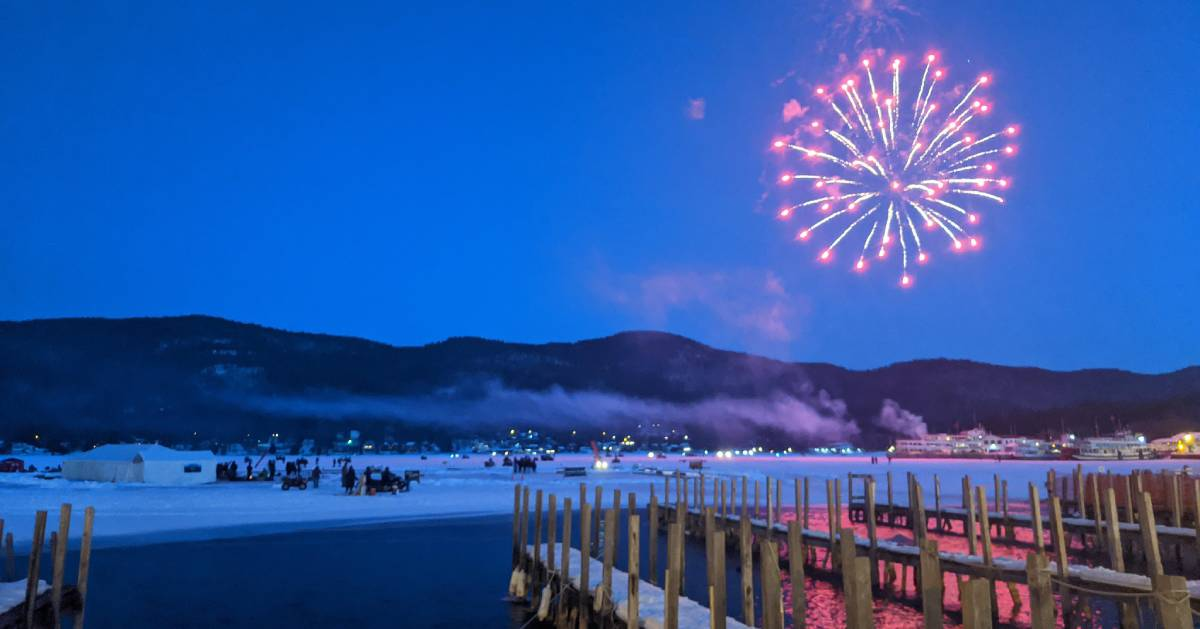 pink fireworks over lake in winter