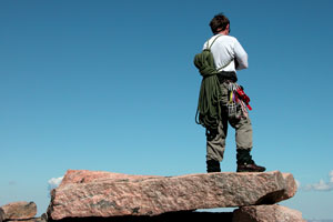 hiker carrying bundle of rope standing on top of a flat rock