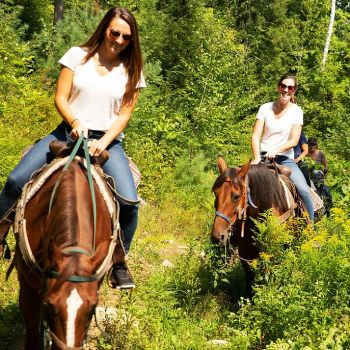 women riding horses on a trail