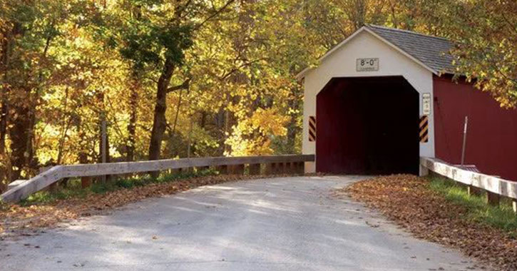 a red covered bridge in the fall
