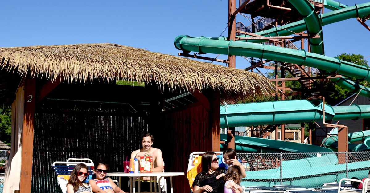 a family in a cabana at enchanted forest water safari, with a large waterslide in the background