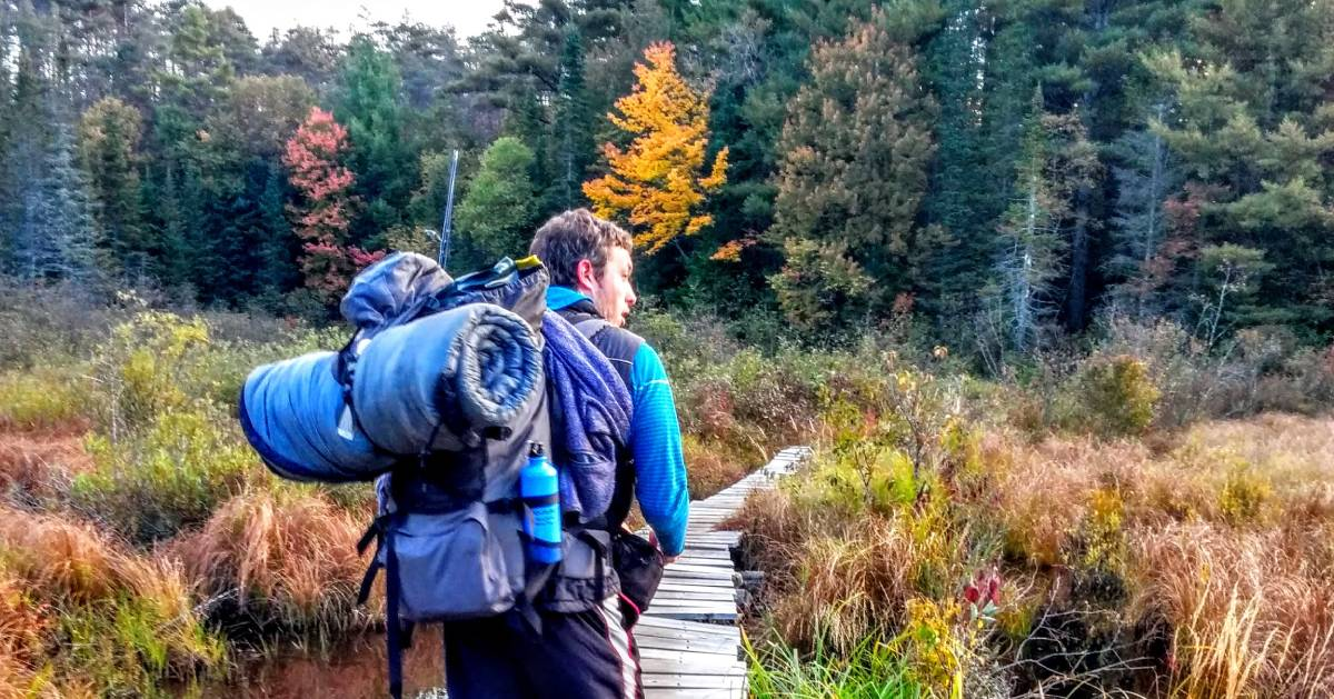 man with camping gear heading into woods in fall