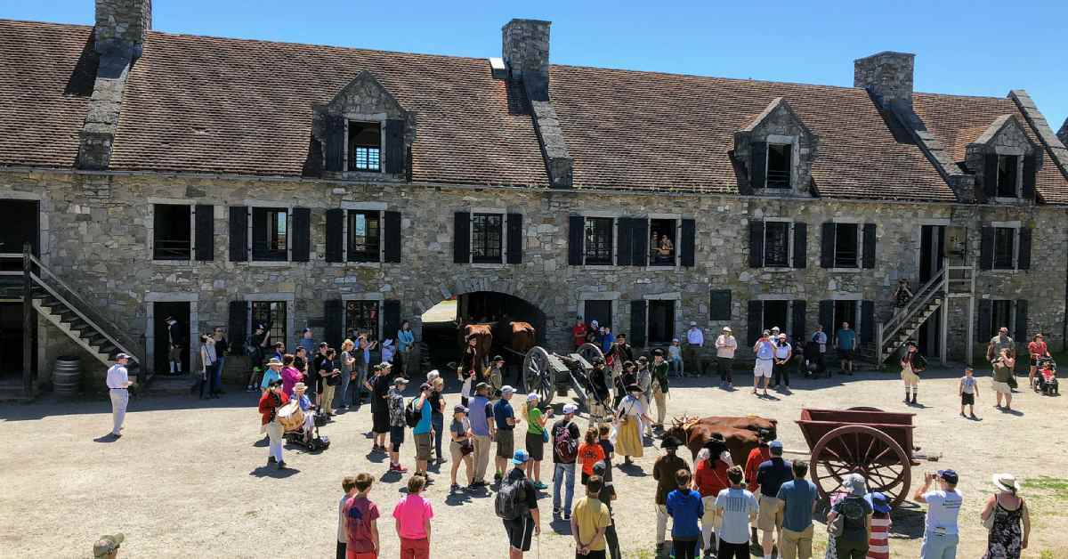 crowd outside a large stone building at fort ticonderoga