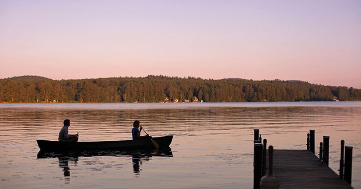two people in a canoe on the lake
