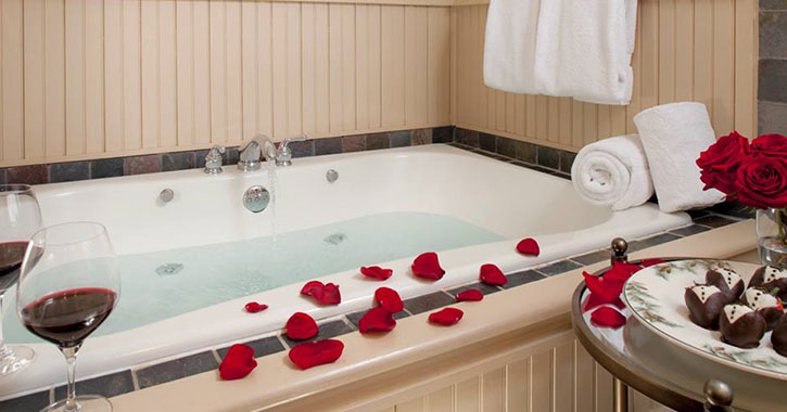 rose petals and wine near a jacuzzi tub