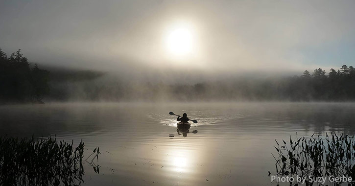 person kayaking on a foggy lake