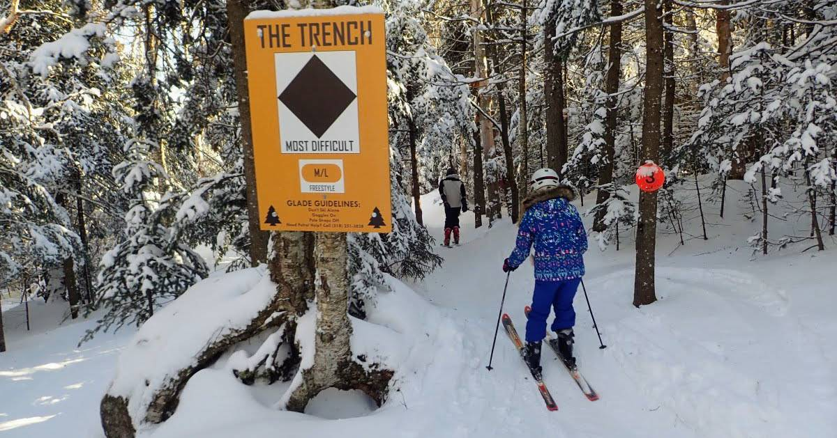 glade skiers in woods by sign