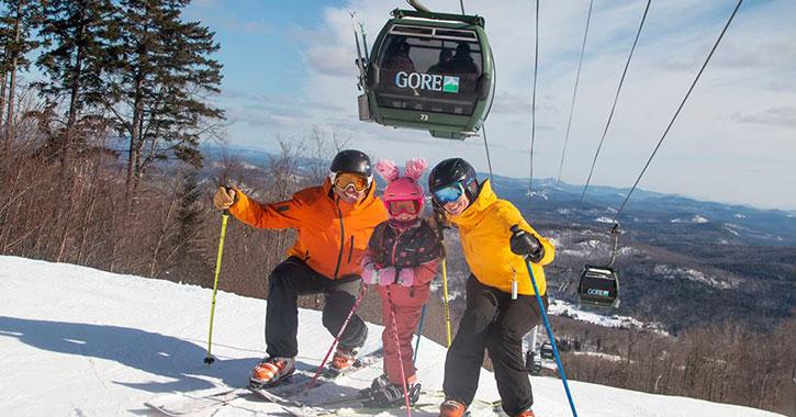three skiers under a gondola