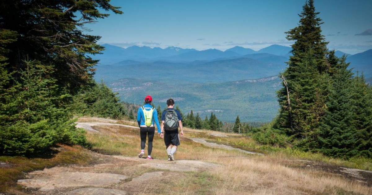 two people hiking on a mountain trail