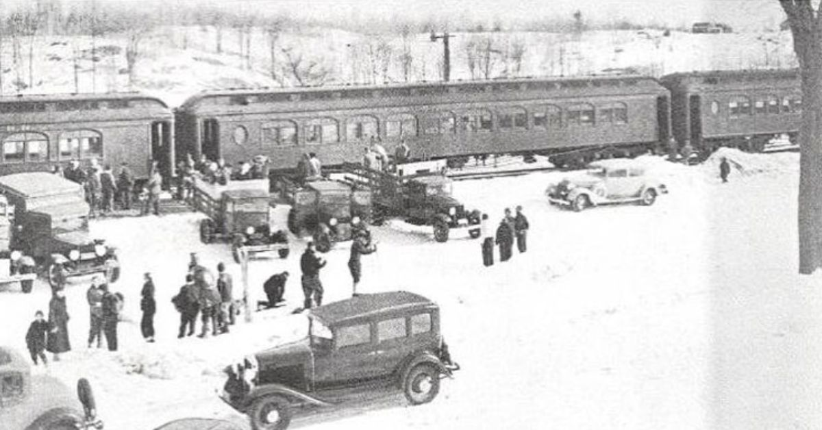 black and white image of people outside a train in winter
