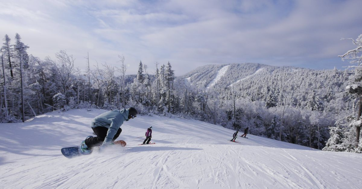 people skiing and snowboarding down a snowy mountain