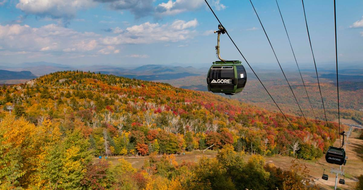 a gondola at a ski resort with fall colors on the trees