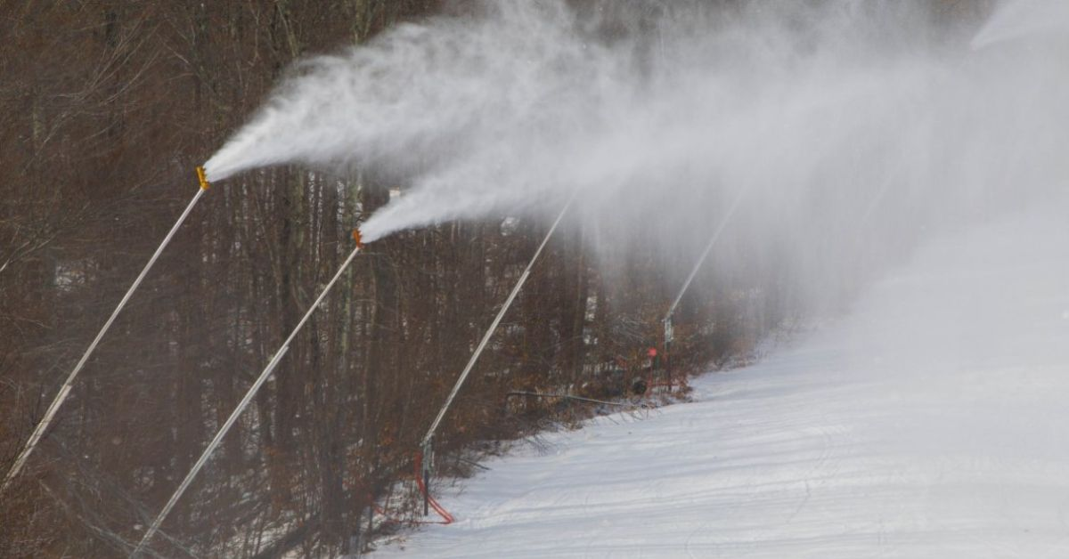 snowmaking machines blowing snow onto trails