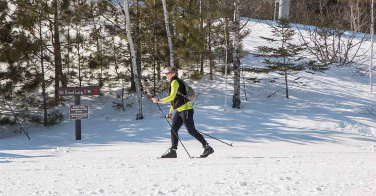 a woman cross country skiing across snowy trail with a sign nearby