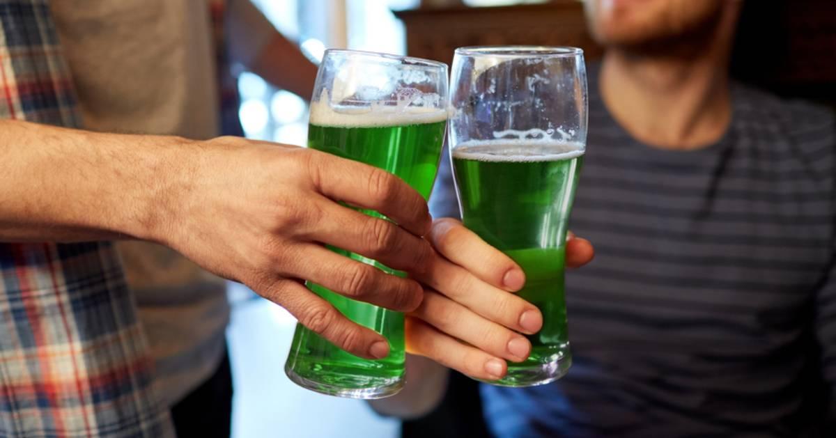 two beers cheersing - green beer