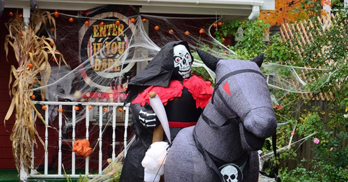 Halloween decorations at house, including blow up skeleton on horse
