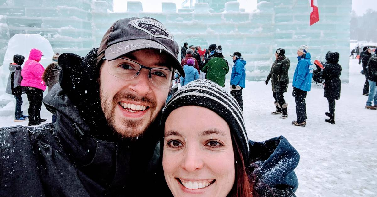 a couple taking a selfie in front of ice palace