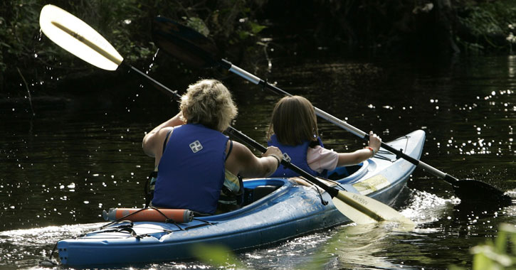 the backs of a woman and young girl kayaking in a double kayak
