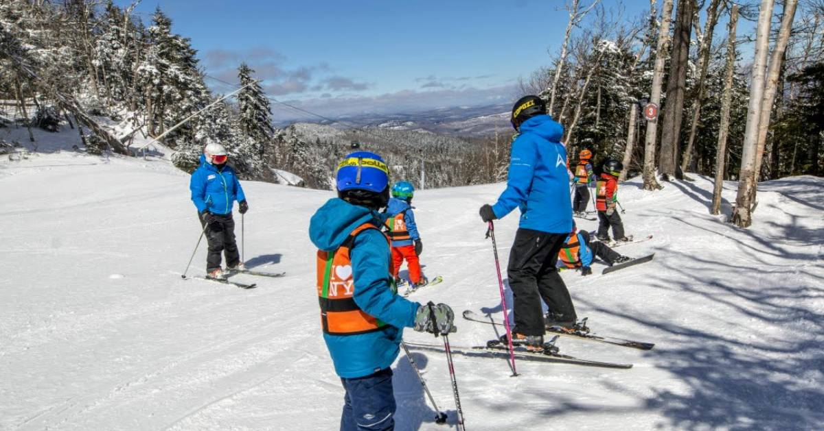 group of kids and adult in ski gear on mountain