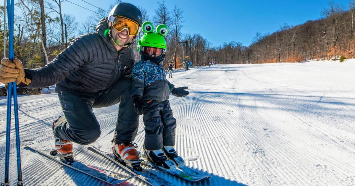 a dad and kid on skis, kid has green frog helmet