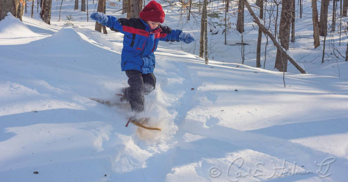kid on snowshoes jumps in snow