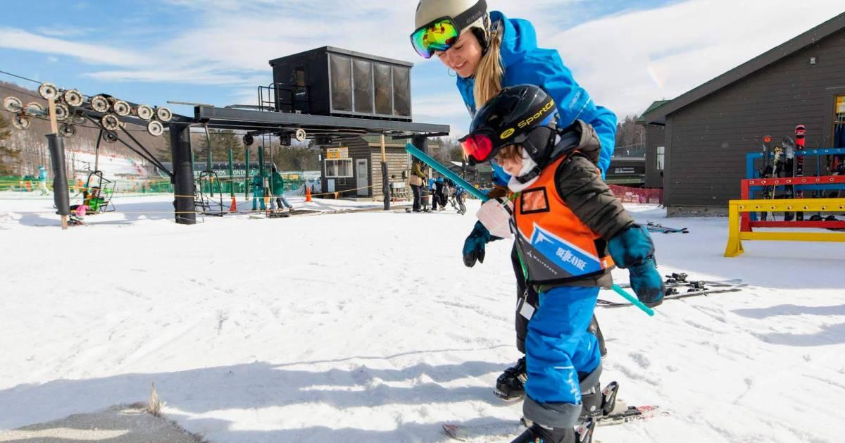 mom helping little boy ski