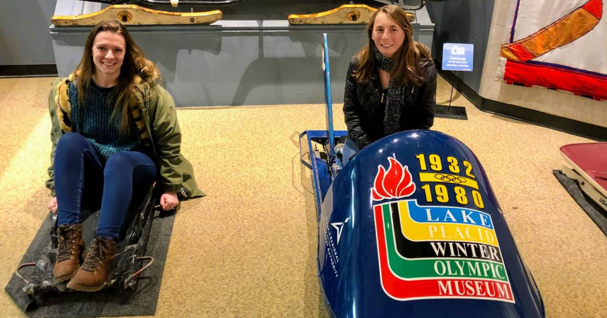 two women posing on bobsleds at museum