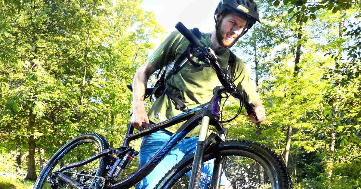 mountain biker carrying his bike