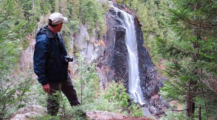 hiker with a camera stands on a ledge looking behind him at the waterfall
