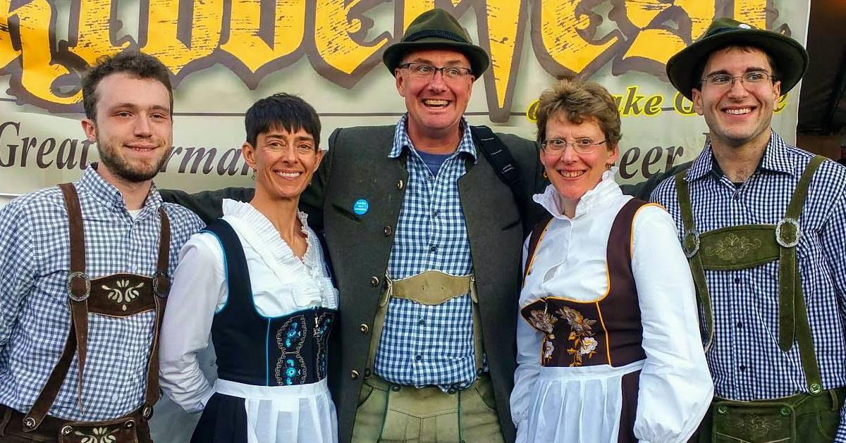 people in German clothing posing by Oktoberfest sign