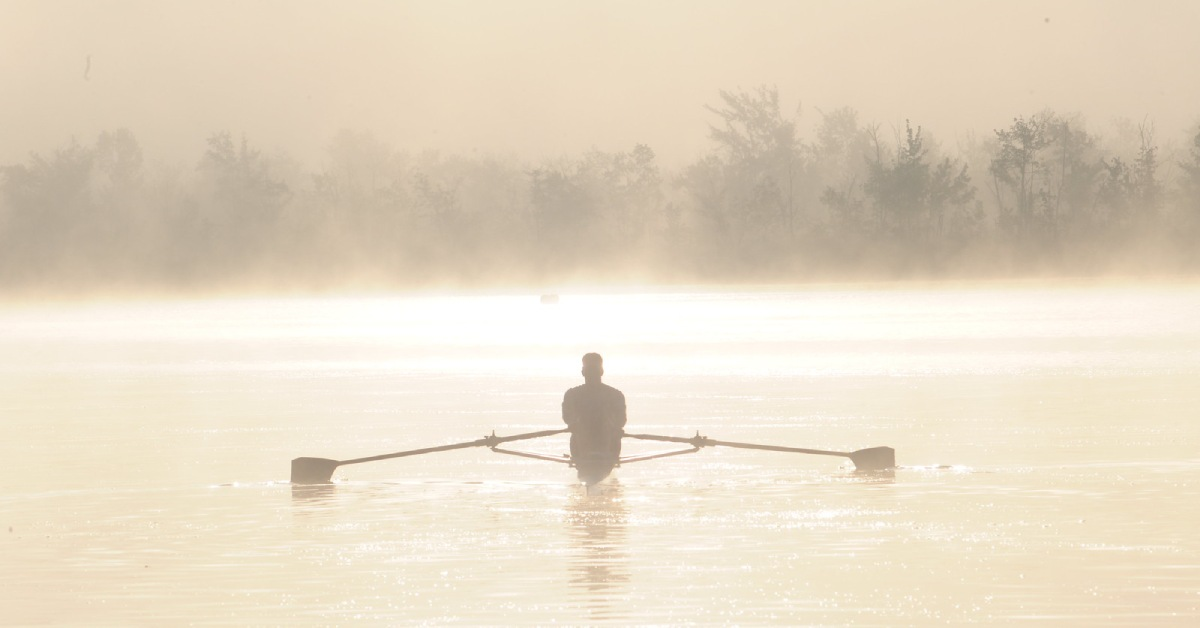 a person paddling on a misty lake