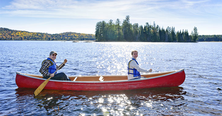 people paddling in a red canoe