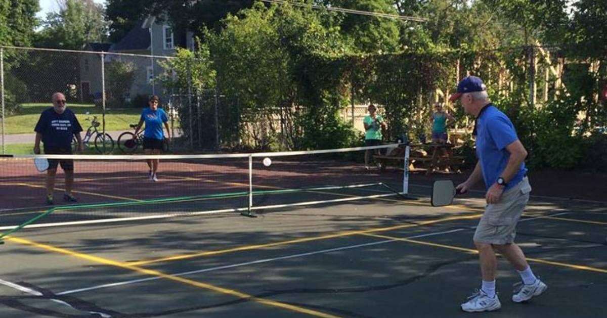 group of four playing pickleball on an outdoor court