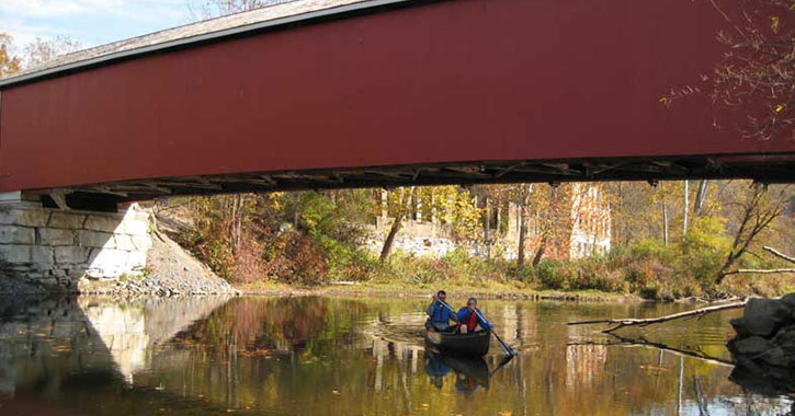 a long red covered bridge with people paddling underneath