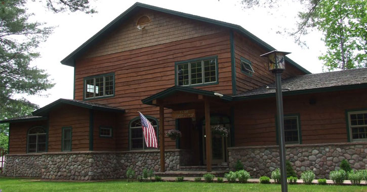 a large, Adirondack-style house with wood panneling and an American flag out front