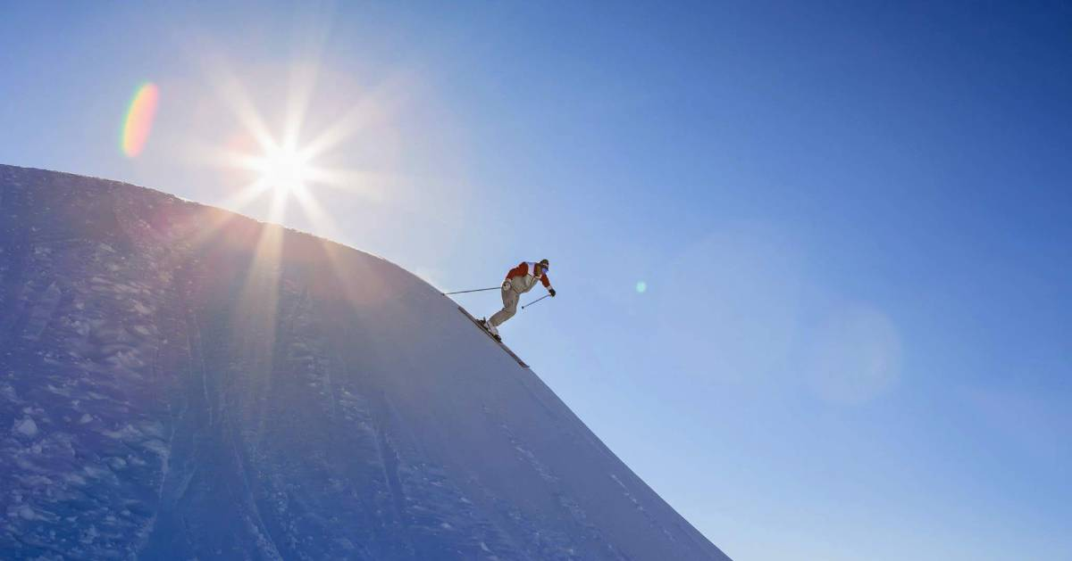 a skier on a steep hill with the sun behind him